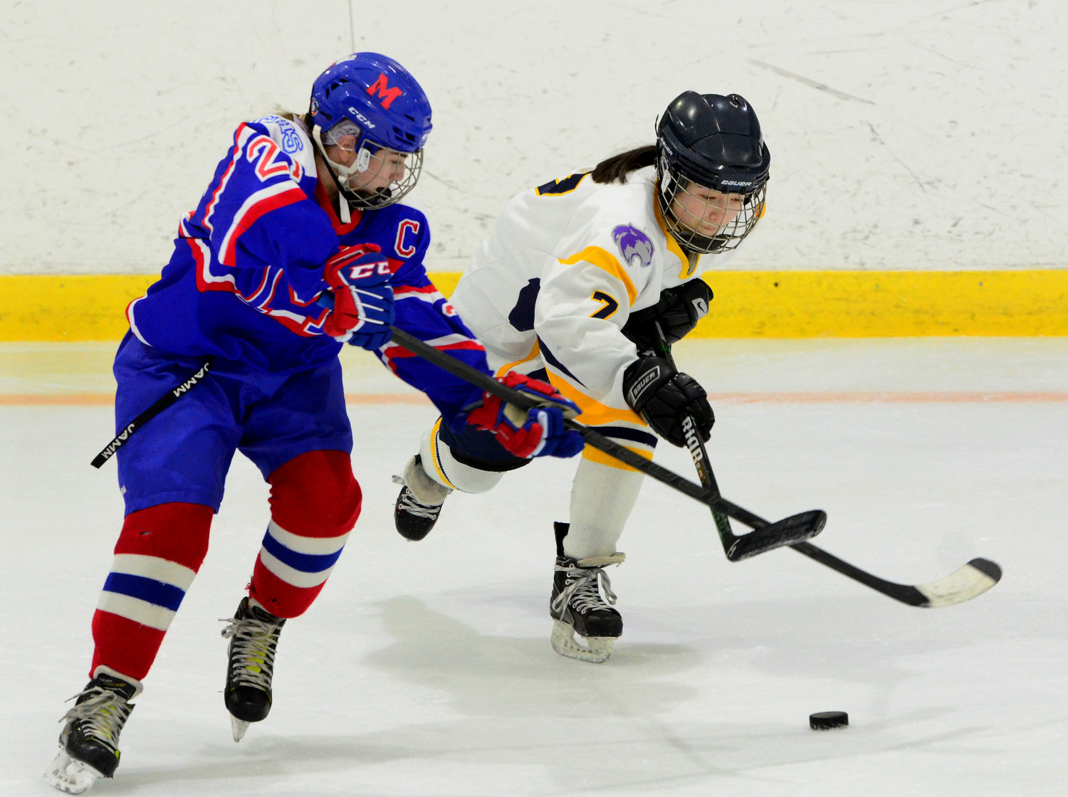 Defenseman Layla Rappleye fights for a loose puck in the defensive zone.