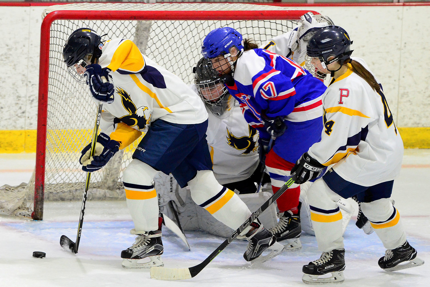Senior defenseman Ella Hanley skates the puck out of the goal mouth with goaltender Ellee Kopecky and forward Marissa Levreault (right).