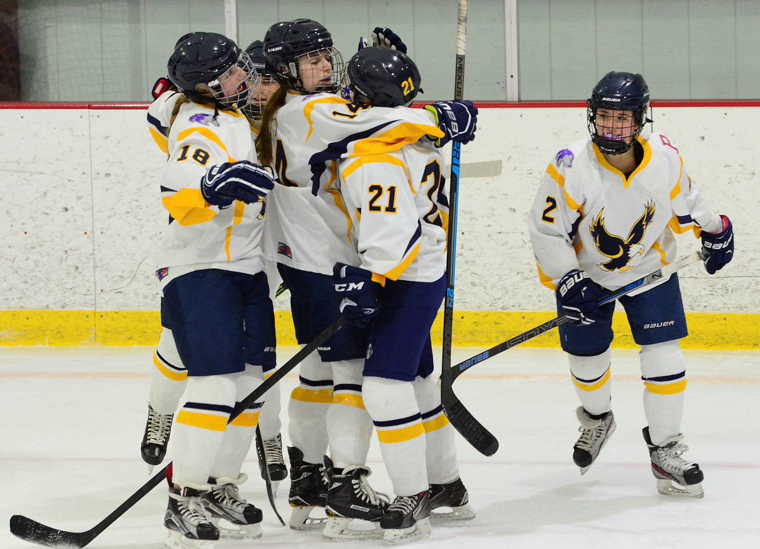 lla Hanley (left) and Peyton Whittet and other teammates swarm teammate Sarah Yee after she scored her second goal in the second period with (Maeve Harrington (right).