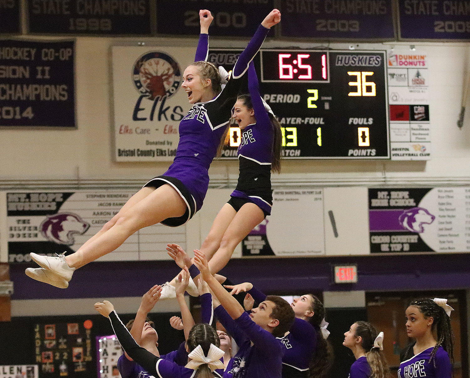 Huskies cheerleaders Angel Bzdula (left) and Rachael Ward are hoisted into the air during their halftime show.