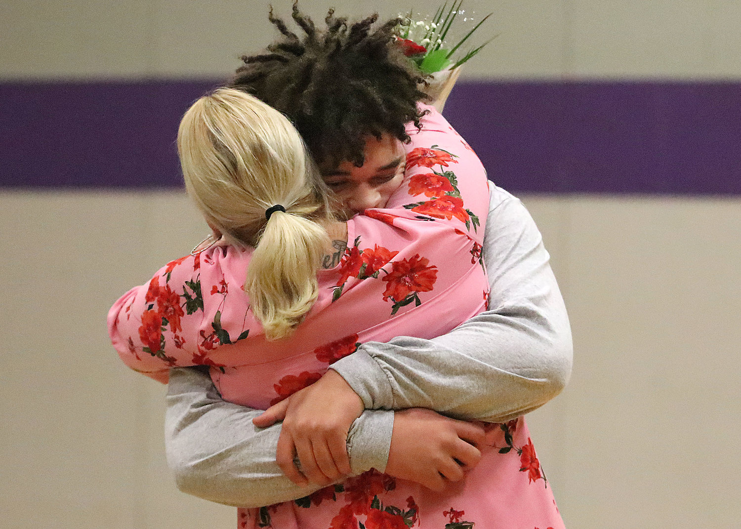 Senior Jalen Kopecky hugs his mom, Jodi during a senior night presentation before the game.