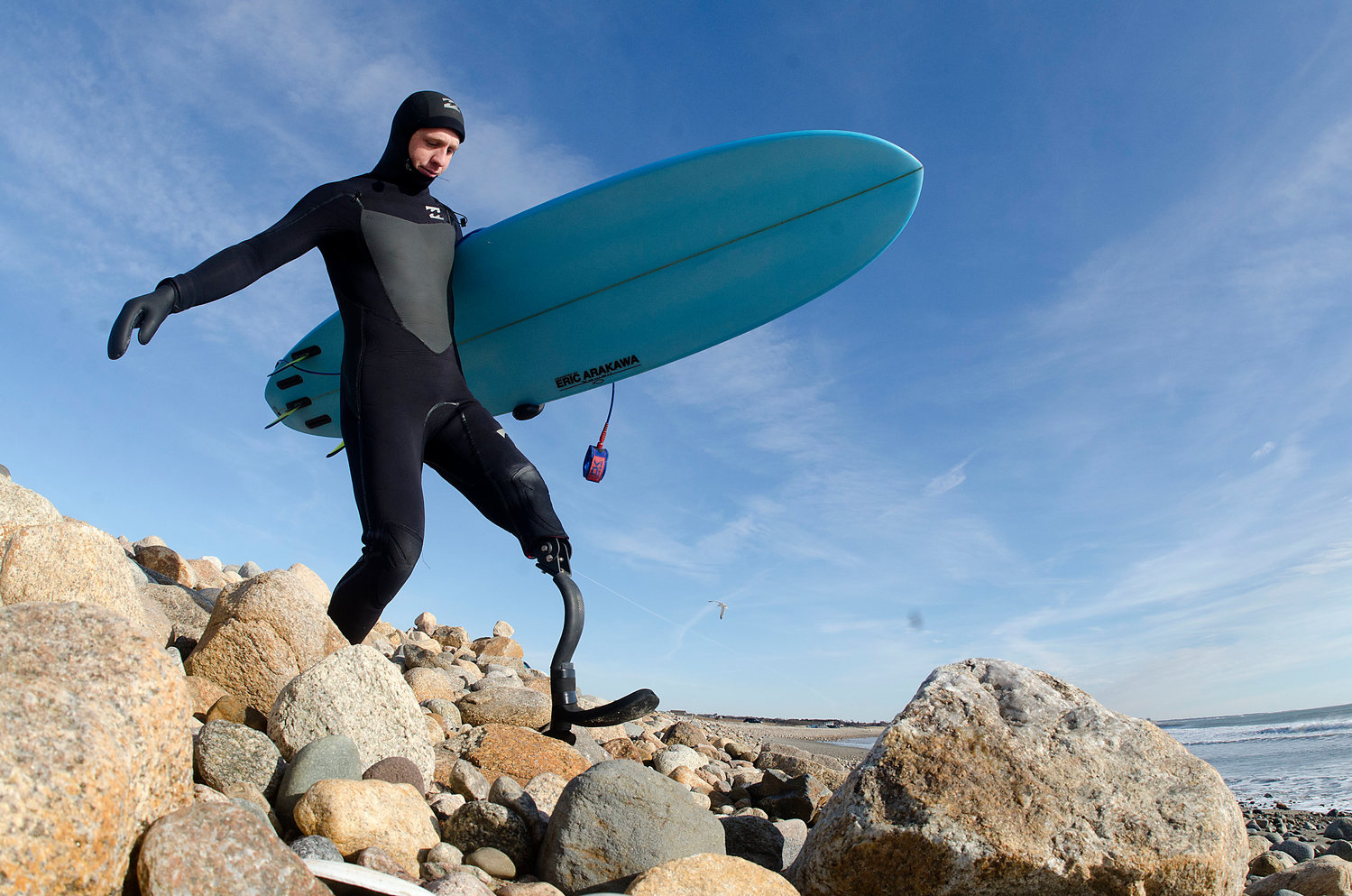 Colin Cook climbs down the rocks at Little Compton's South Shore Beach nearly two years after the shark attack that claimed part of his left leg. He's wearing an early-version carbon fiber limb designed and built for him by Sakonnet area friends especially for use while surfing.