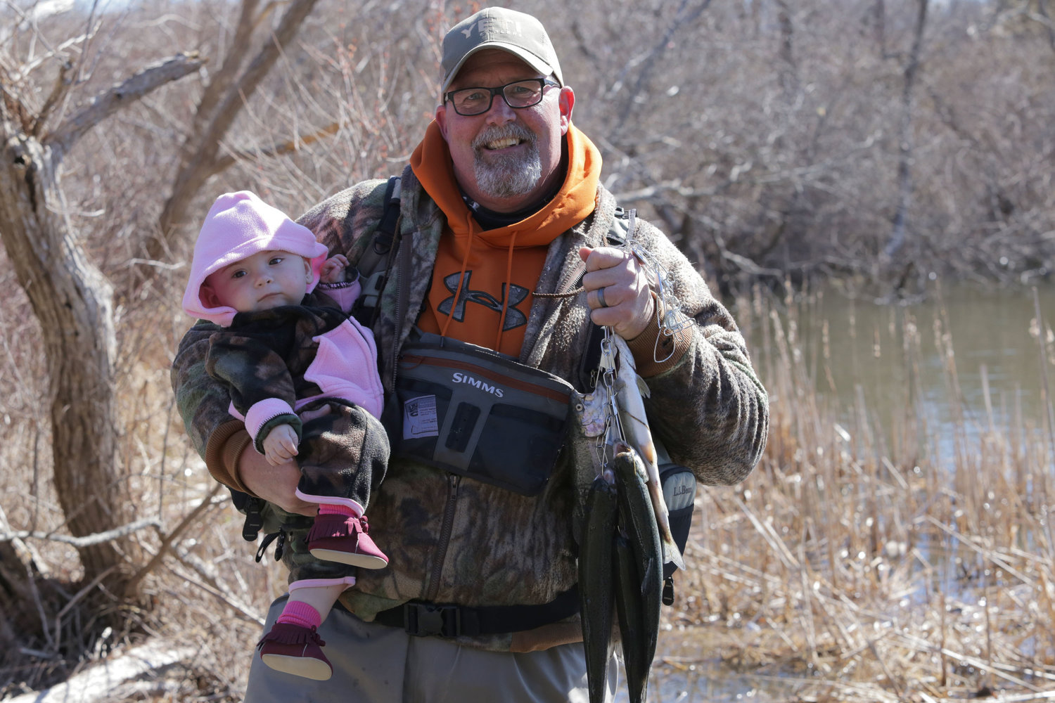 Ron LaChance, holding his 11-month-old granddaughter, Madiana Holt, poses with his limit of five trout at Melville Pond on a previous opening day. (File photo).