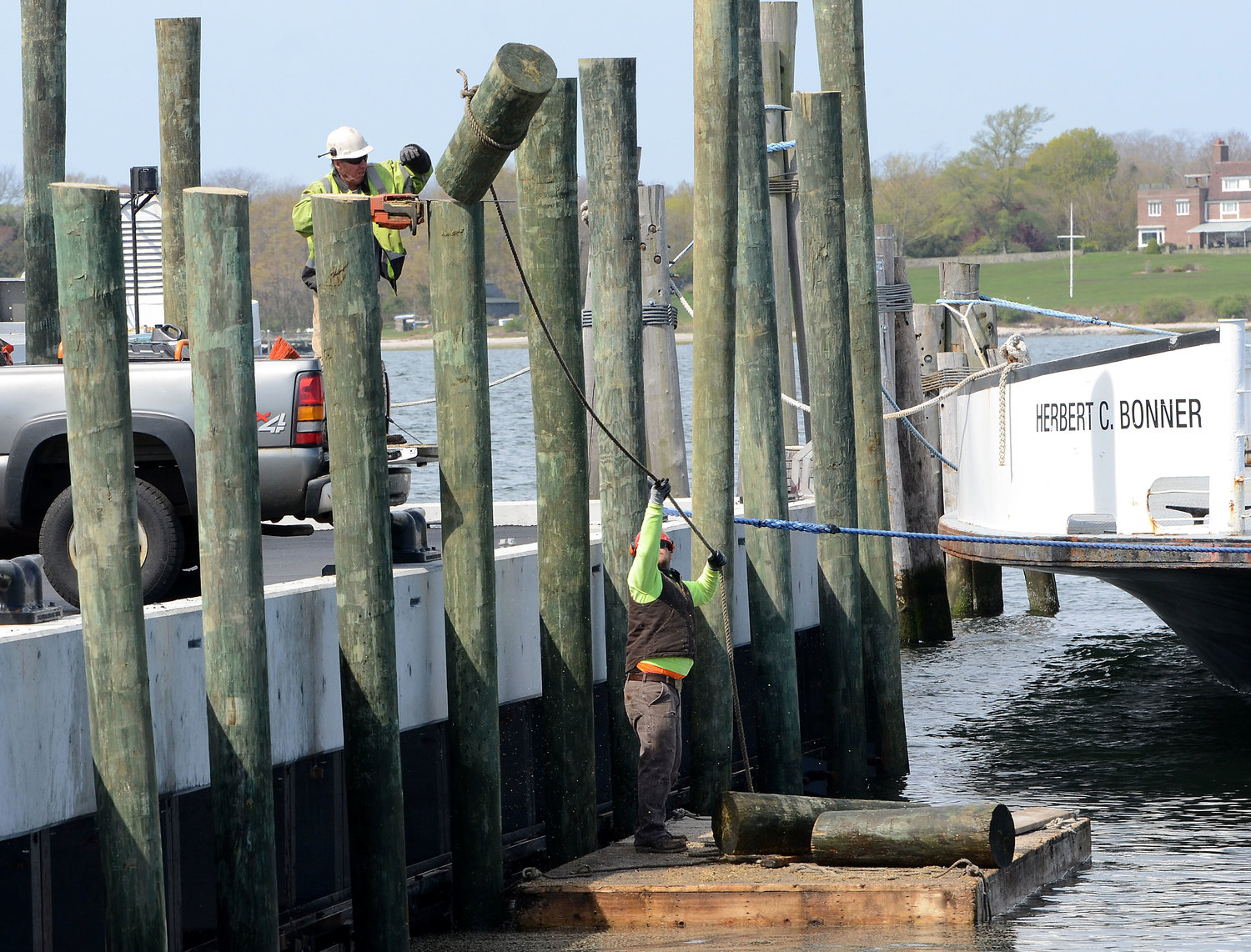 New England Building and Bridge worker Bobby Guilford (left) lops off the top of a pier pole while coworker Kevin Stewart guides it as it falls into the sea as they put the finishing touches on the Prudence Island Ferry pier last week.