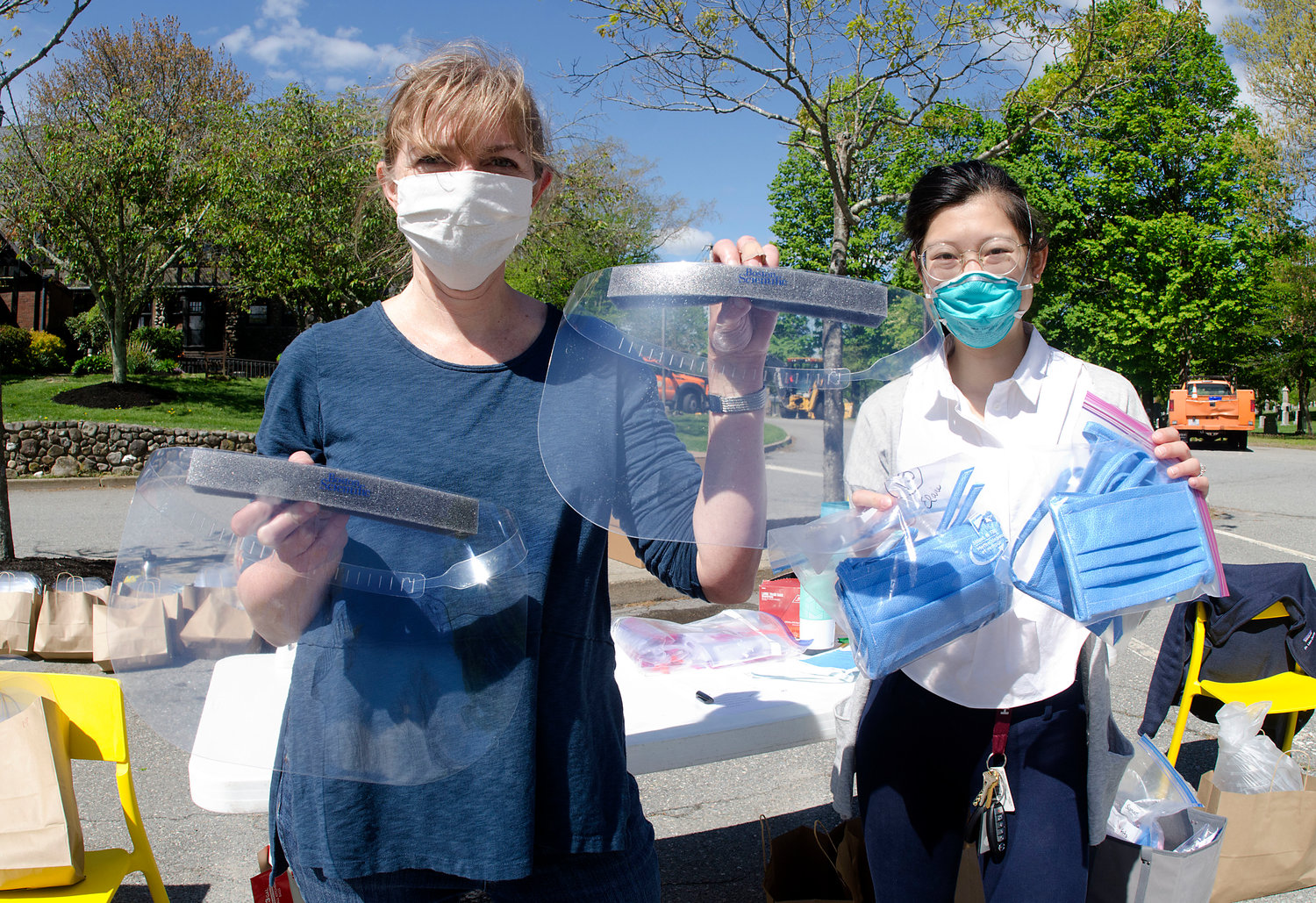 Dr. Lisa Denny of Barrington Family Medicine (left) and fourth-year Brown medical student Vivian Chan Li, of Central Falls, hand out face shields, masks and other various PPE to medical offices and nursing homes on Saturday behind the Barrington Town Hall.