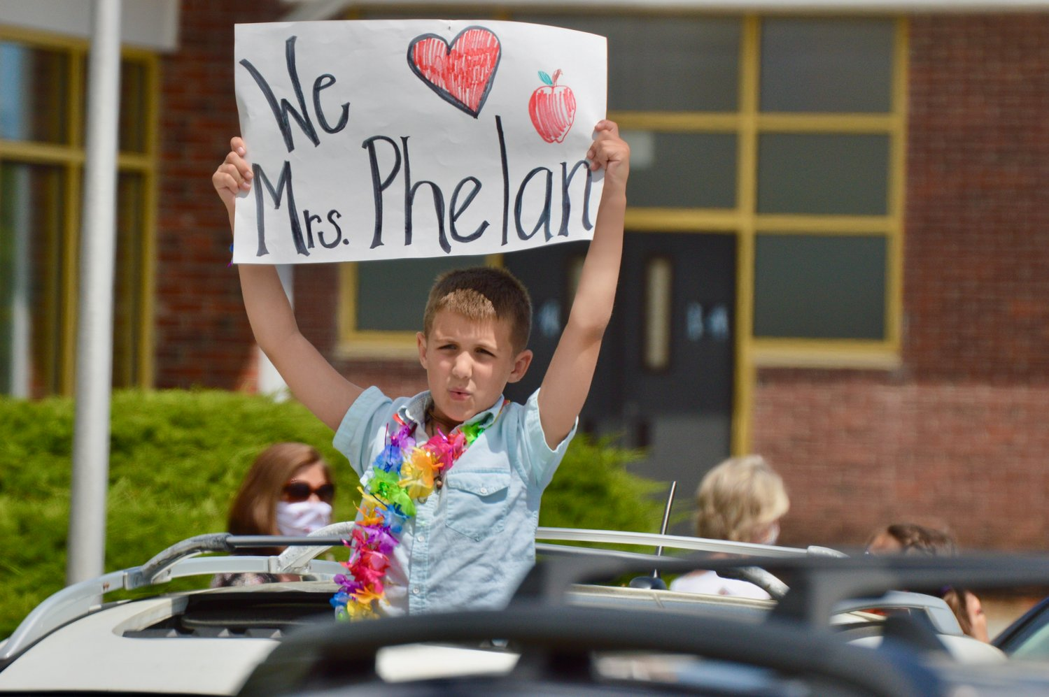 Colin Habershaw displays a special sign for his fourth-grade teacher, Alexandra Phelan.