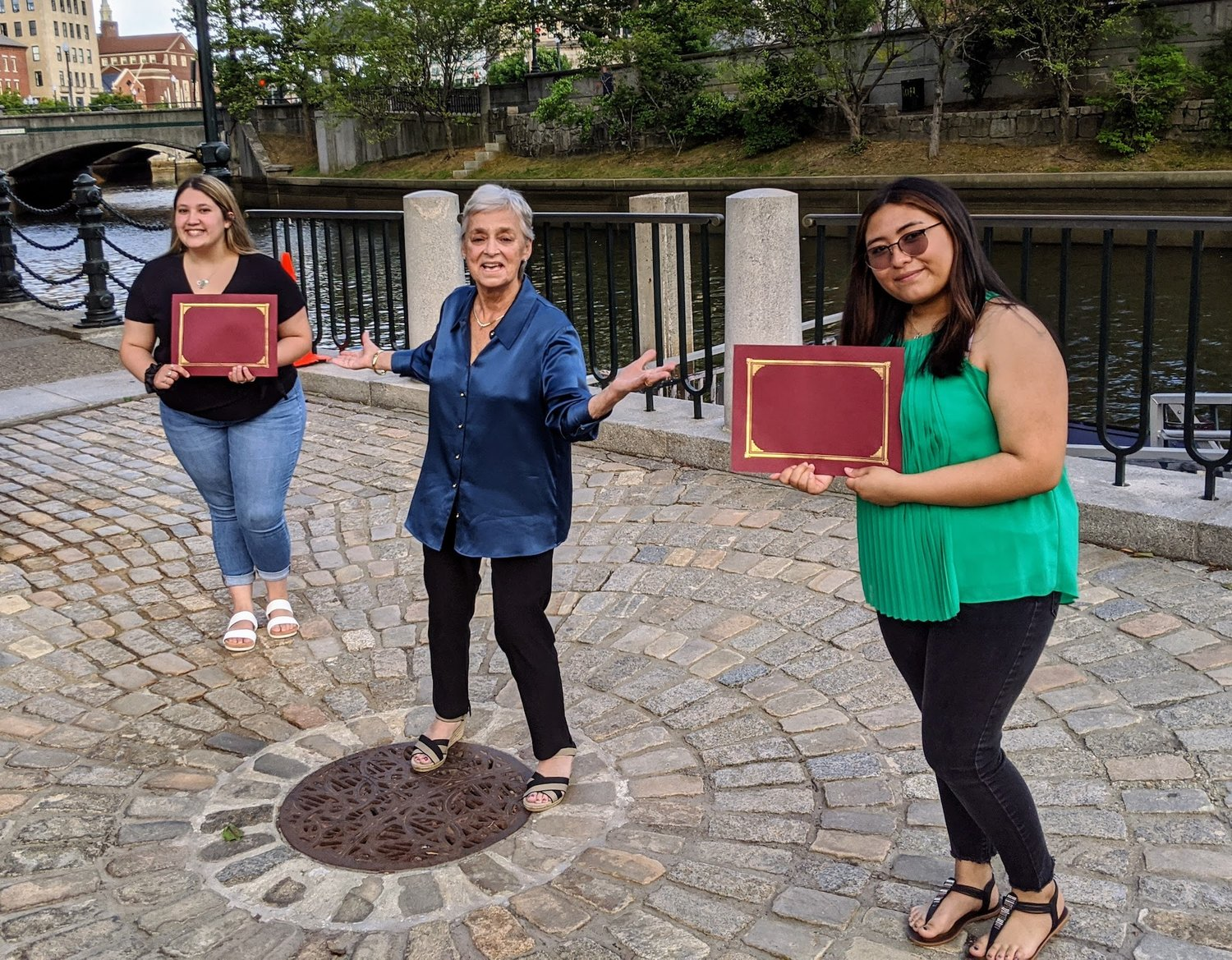 Linda Jane Maaia (center) presents East Providence High School Class of 2020 graduates Maria Lopez (left) and Carol Araujo with teacher scholarships while social distancing by the gondola dock in Providence.