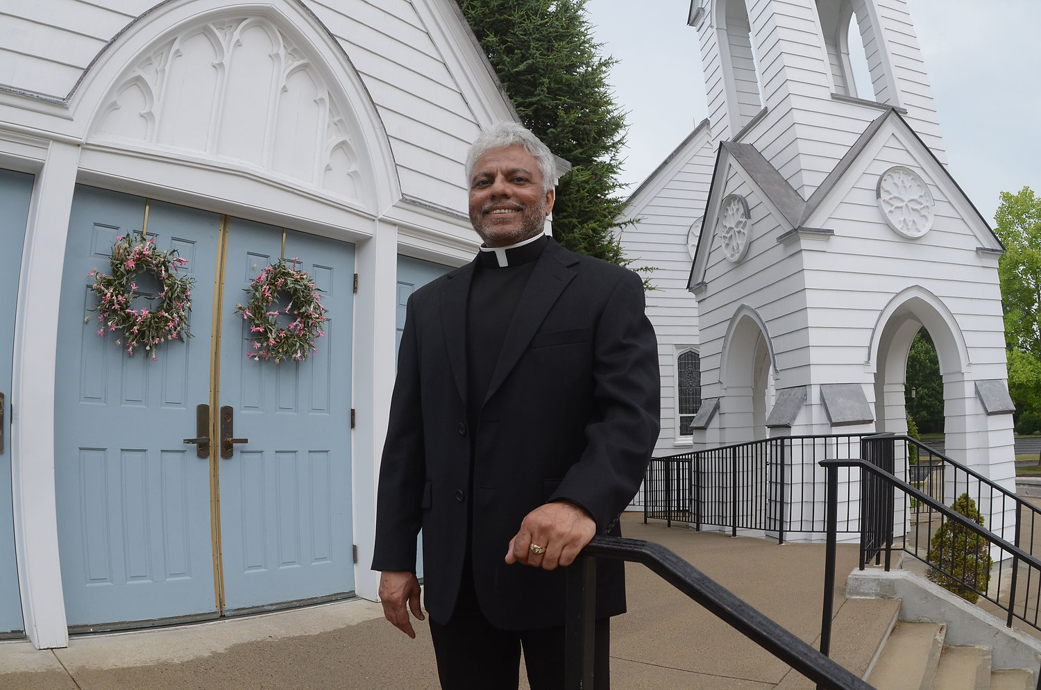 "St. Luke's Church pastor Father TJ Varghese stands in front of the church for a photograph last week. On Sunday, Father Varghese celebrated his final weekend Mass at the Barrington church. This week, Father Varghese starts his new assignment at Mary, Mother of Mankind parish in North Providence. ""I am going to miss this place. It is a jewel,"" Father Varghese said of St. Luke's."