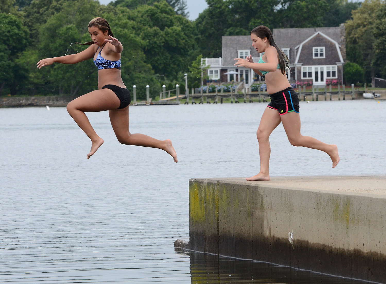 Ella Patalano, 11, (left) and Samantha Cygawnos 12, jump off the wall at the Warren Town Beach Monday afternoon.