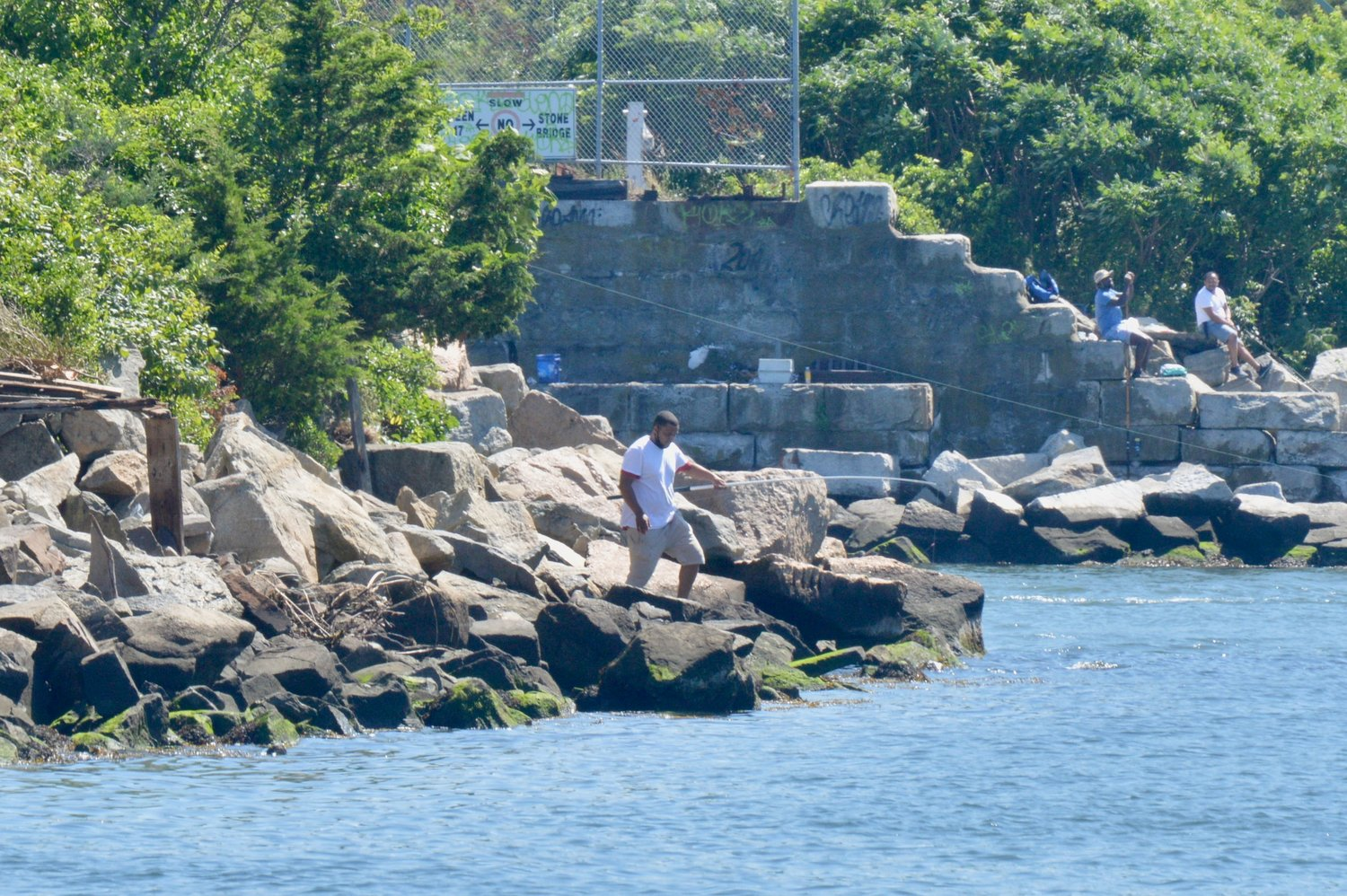 "Visitors fish from the rocks off the railroad tracks near the Sakonnet River Bridge. ""They're coming down here with babies, children. If any one of those kids fell off from those rocks and into the water, I don't know if anyone could get to them,"" said Vicky Newbold, who lives under the bridge."