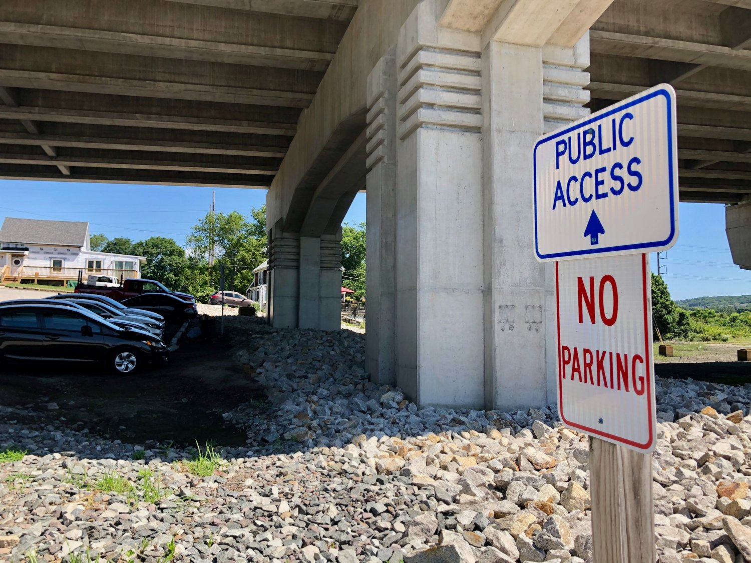 A sign erected by the state marks the public access point under the Sakonnet River Bridge. A potion of a legal parking lot is at left.