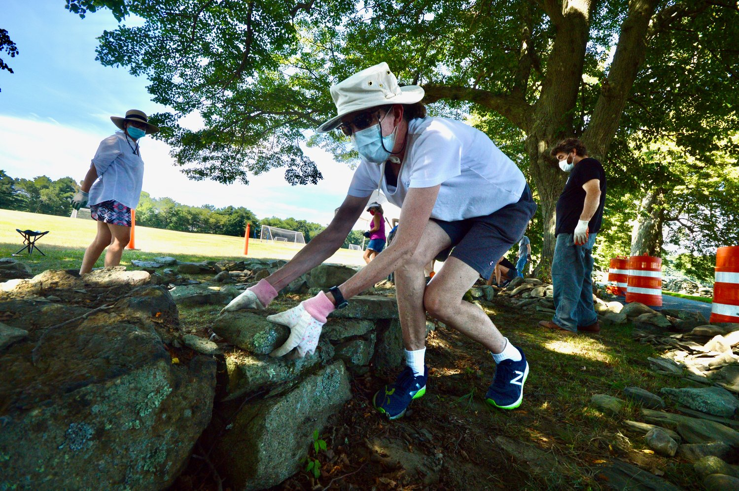 "Kathryn Hannabury of Portsmouth removes a stone from a wall along Linden Lane at Glen Farm during a volunteer training session on July 27. ""There's clearly a lot of thought put into the process of how to build a good wall versus the wall that will collapse years down the road,"" she said."