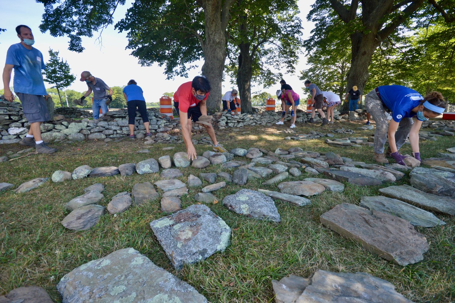 "Volunteers sort stones taken from a damaged wall at Glen Farm during a training session on July 27. ""It's a little more efficient way to build,"" said Mr. Faraone."