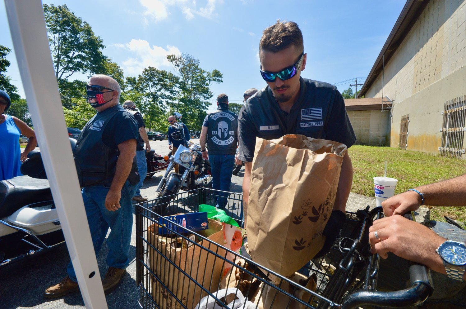 Evan Luther, a member of the Watchkeepers Rhode Island motorcycle club, loads donations from the club into a shopping basket during a food drive Sunday at the Portsmouth Emergency Food Bank on Sprague Street.