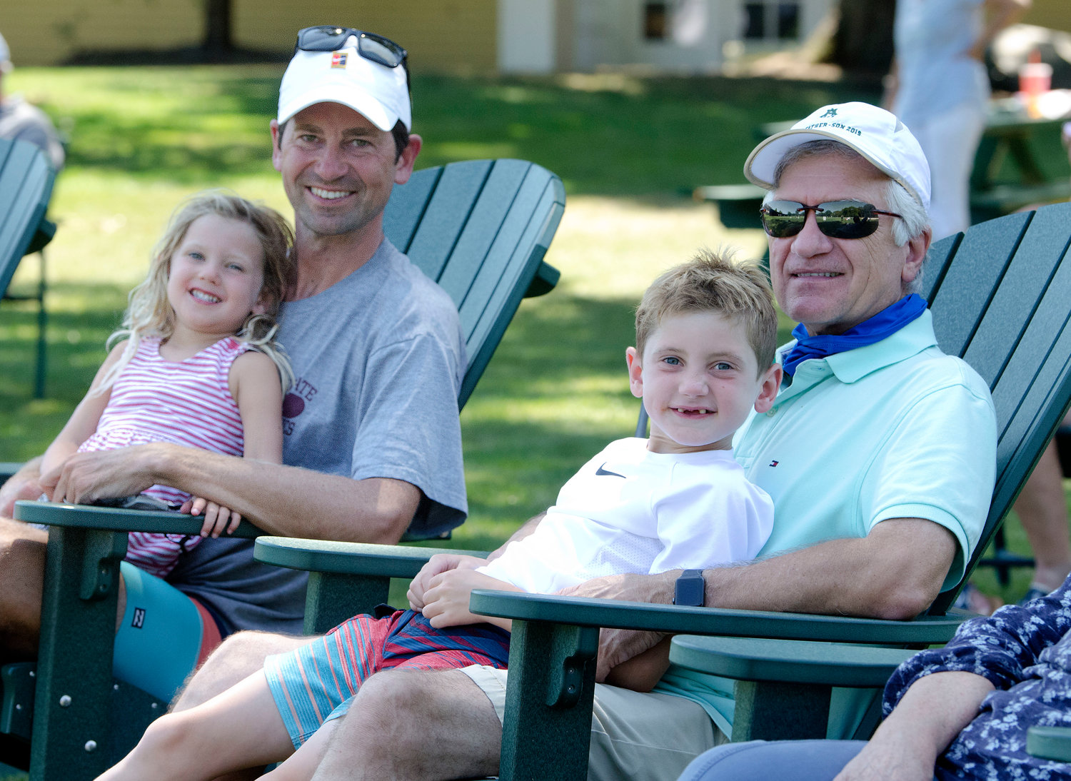 Eventual doubles draw winner Evan Ambrose, with daughter Julia on his lap, along with his dad, Paul Ambrose and Evan's Ryan watch the singles action.