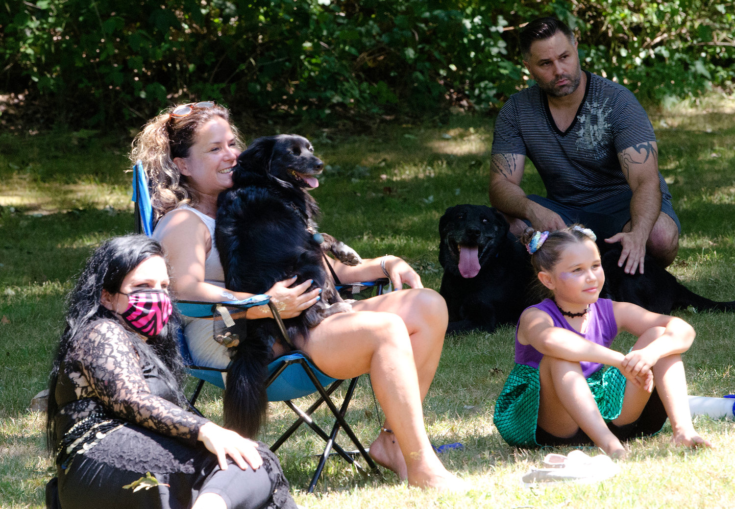 "Susie Dejesus, her dog Onyx, and niece, Harley Souza, watch the ""Sacred Flames and Friends"" dancers during the Looff-East Providence Arts Festival at Hunts Mill on Saturday."