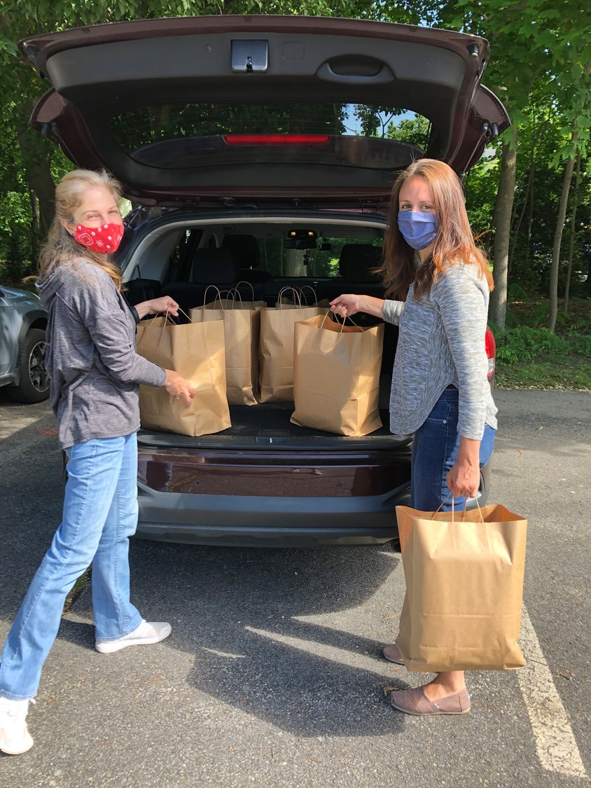 Sarah Mackley of Seven Stars Bakery (left), and Marlene Glasheen, Tap-In volunteer, showcase the first delivery of loaves of bread to Tap-In.