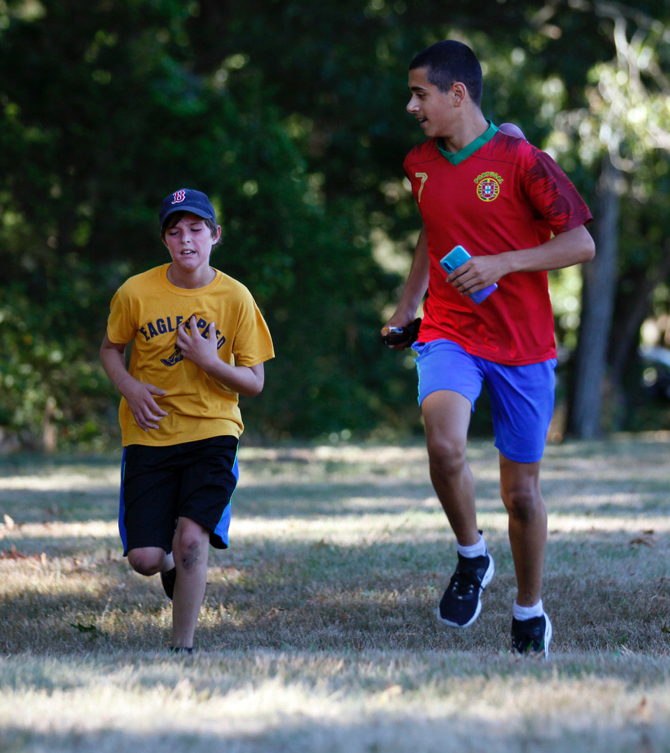 James Schuler, ll, an Eagle Speed member, gets encouragement from former team member Brandon Piedade, 14, who is entering the high school this fall, but ran with Eagle Speed when he was in middle school. They were participating in the only in-person summer workout because of the pandemic..Eagle Speed, a running group for middle school age kids, meets for their one get together during the summer to talk about their progress doing the workouts on their own and run around Haines Park.