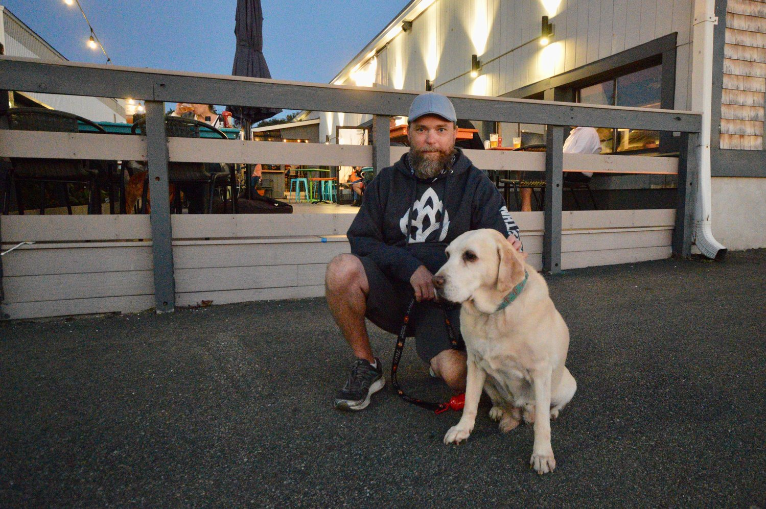 Joe Murphy, one of the three partners at the Gulf Stream Bar & Grille, with Honey, a 12-year-old Lab who acts as the restaurant's mascot. Patrons are invited to bring their dogs onto the outside deck in the background.