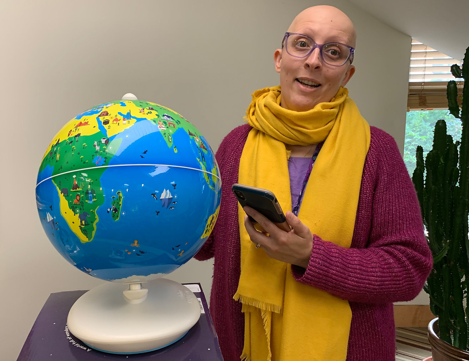 Kristin Amaral shows off Rogers Free Library's new augmented reality globe, which works with a phone app and lets users learn about various cities and countries when they point to a location on the sphere.