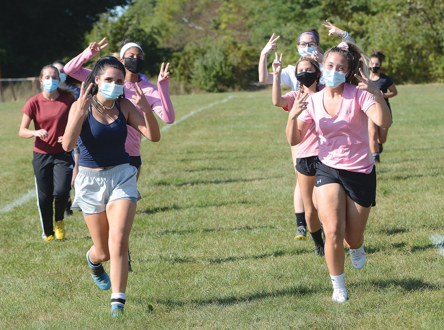 Tiverton girls soccer captains Sydney Silvia (left) and Mariah Ramos (right) and teammates celebrate their return to the field as they jog at the start of practice Monday.