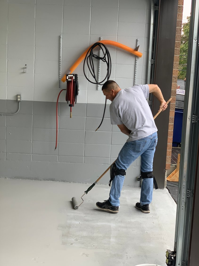 Patrolman John Mlynek applies a new finish to a garage floor inside the newly refurbished Bristol Police Station. Two officers have been temporarily taken off the streets and assigned to make a host of building improvement.