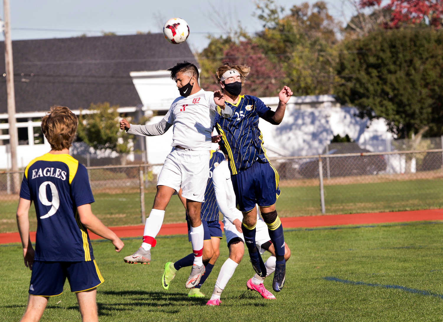 Gabe Ferriera heads the ball beats a Barrington opponent to a head ball during Saturday's game, in Barrington.