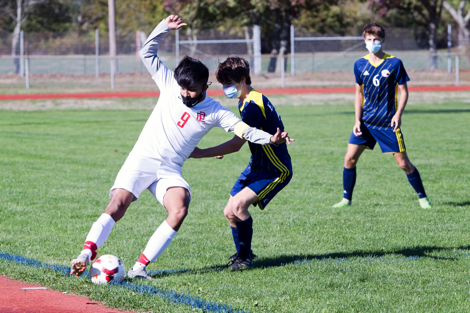 Gabe Ferriera attempts to keep the ball in play, under the pressure of a Barrington opponent.