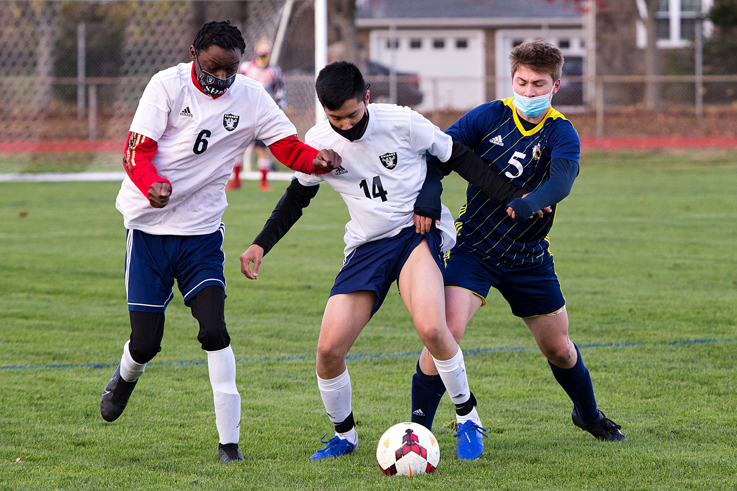 Samuel Faulkner battles a pair of Shea opponents for possession of the ball. Barrington beat Shea, but lost to South Kingstown in the playoffs on Monday.