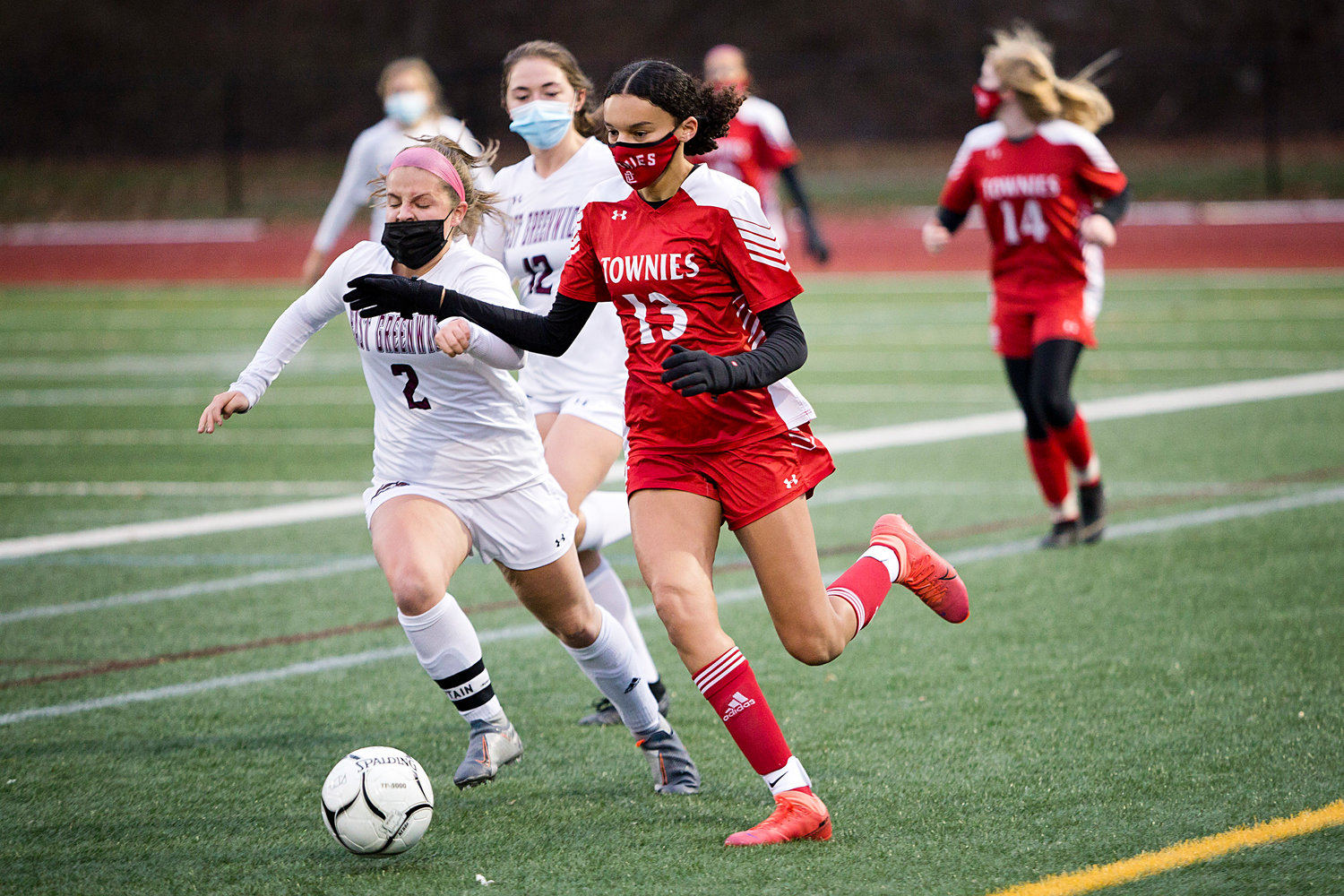 McKayla Lopes controls the ball up-field under the pressure of an East Greenwich opponent