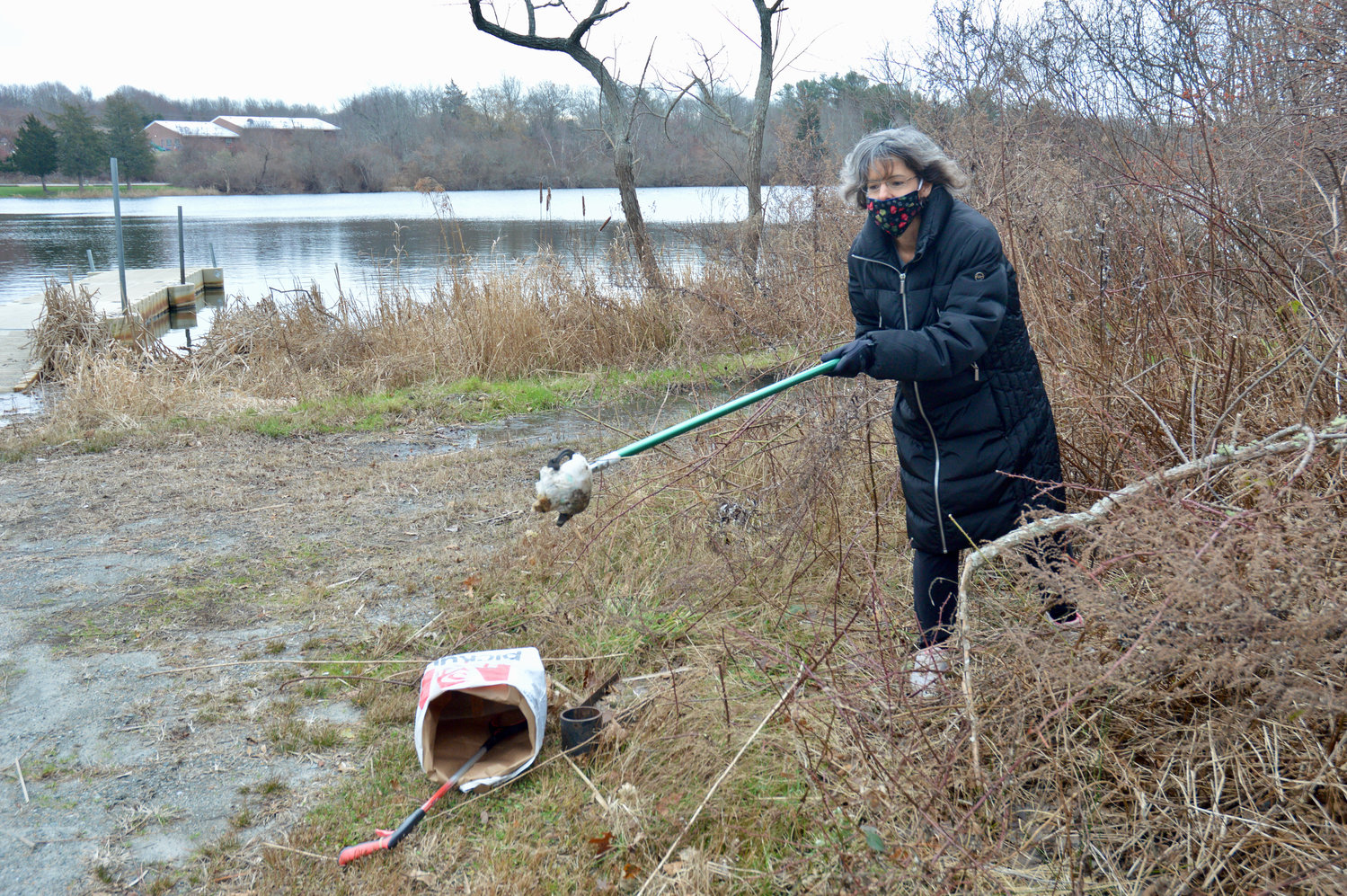 "Jen Haga uses a trash-picker to collect a dirty diaper she found near the Thurston Gray Pond at the Melville Park Recreation Area Tuesday morning. A member of the town's Solid Waste and Recycling Committee, she recently ""adopted"" the spot to clean up on a regular basis, and is hoping other residents will join her in adopting their own areas."