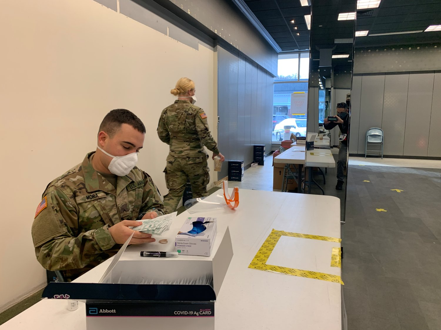 RI National Guardsman Darrien Mora readies packs of swabs at the pop-up testing site inside the Barrington Shopping Center on Tuesday morning.