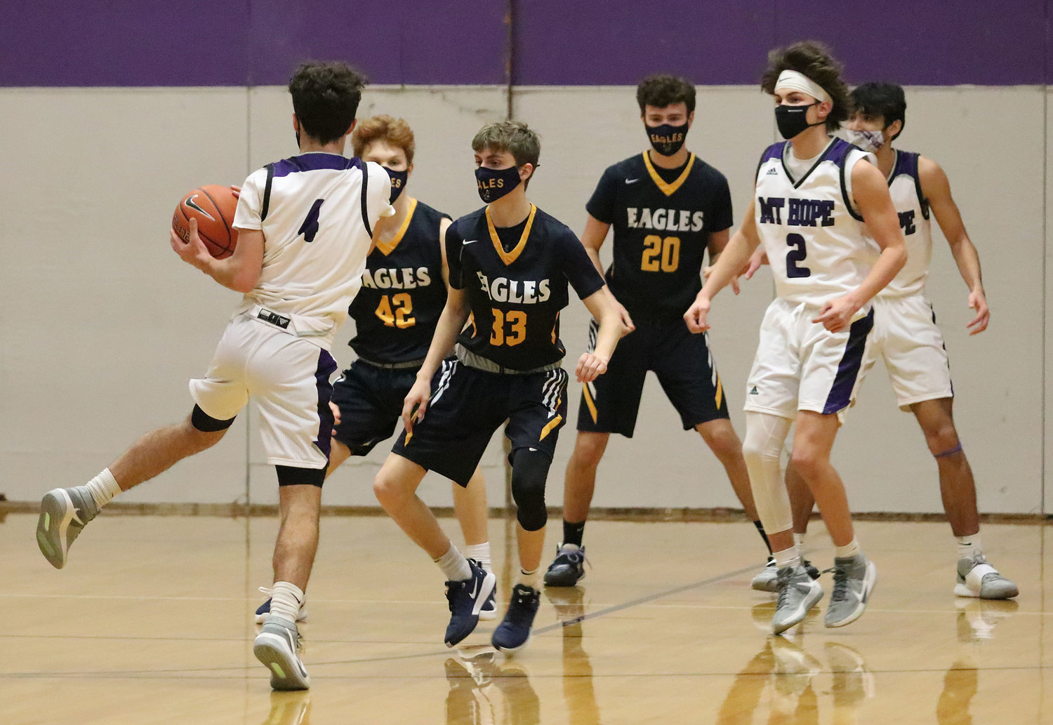 Barrington defenders Brigham Dunphy (left), Sean Bonneau, and Nick Scandura get into their defense as Mt. Hope's Parker Camelo brings up the ball during a non-league game in Bristol on Monday night. Barrington won 77-40.