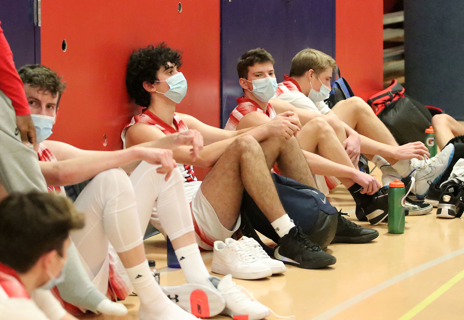 Members of the PHS boys' varsity basketball team rest after defeating Chariho on Saturday. Running up and down the court with a mask on is grueling, one player said.
