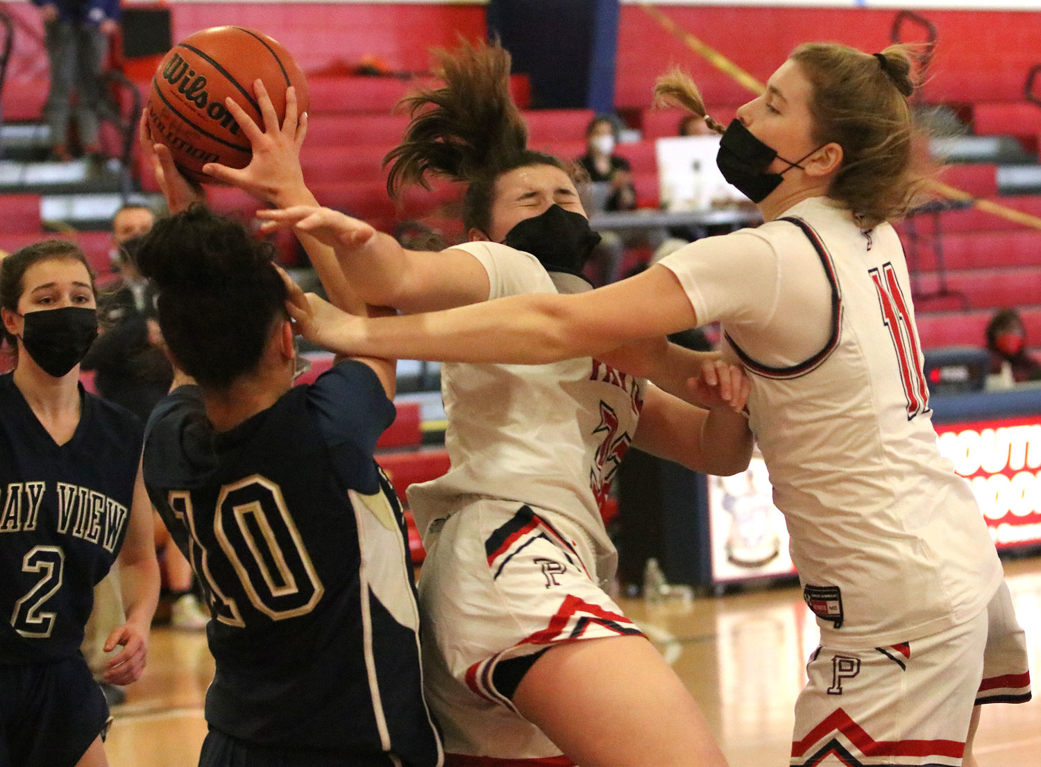 Patriots senior guard Emily Colicci (left) and Maeve Tullson vie for a rebound under the Portsmouth hoop.