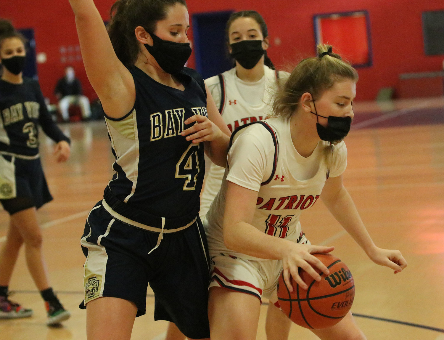 Patriots forward Maeve Tullson puts the ball on the floor in the offensive zone, with Olivia Durant looking on.