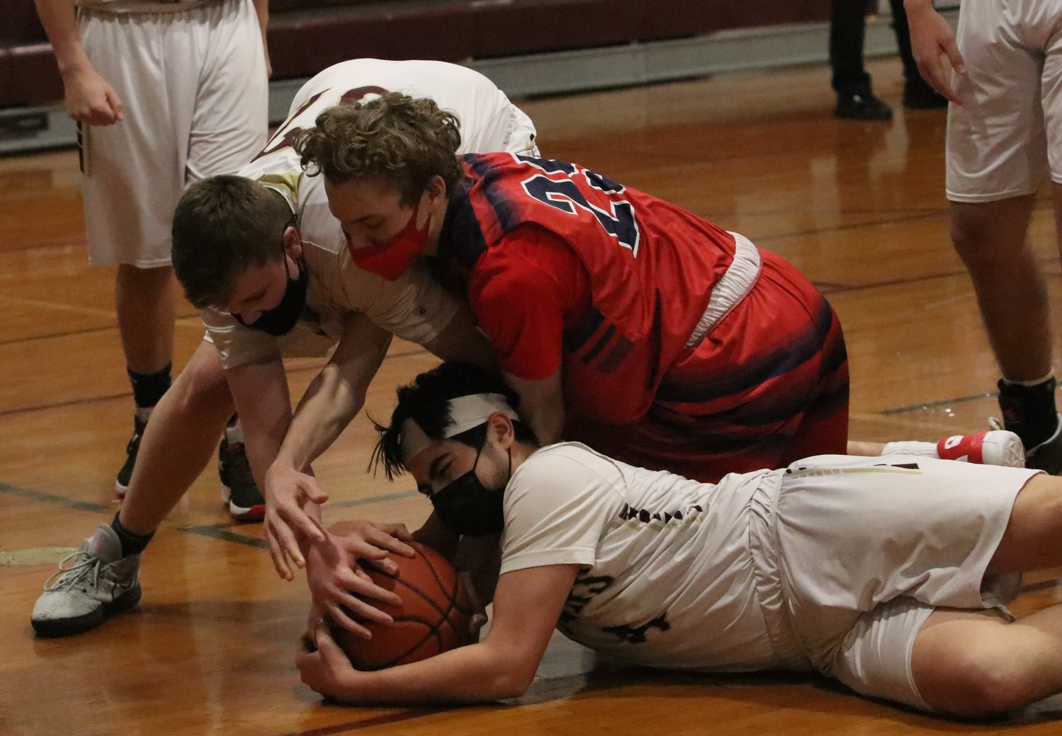 Sophomore forward Jason Potvin (left) reaches in as teammate, Junior guard Luke Deldeo grabs a loose ball on the floor in the defensive court.