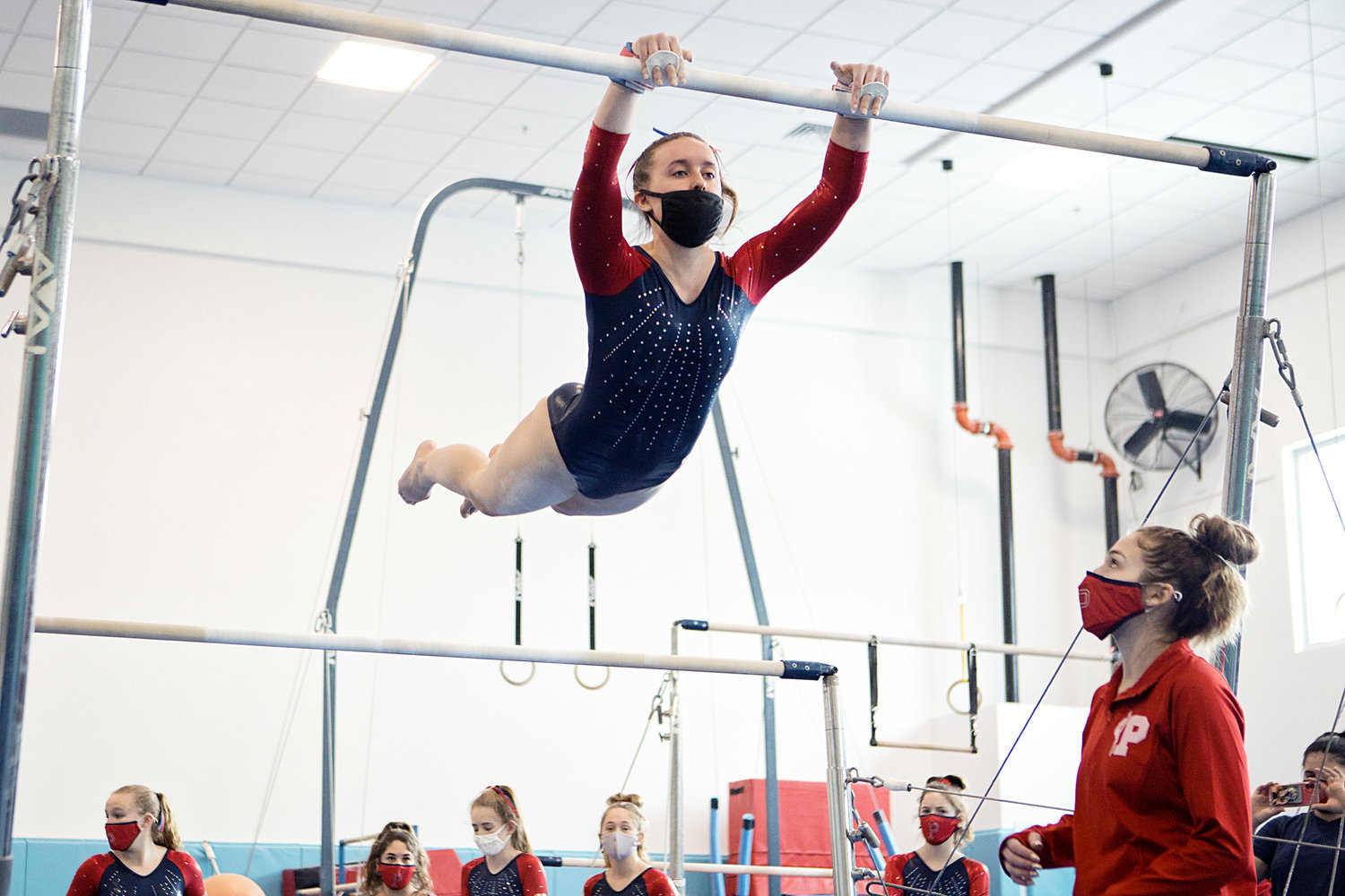 Fiona Daly swings to the high bar while competing in the Region 1 