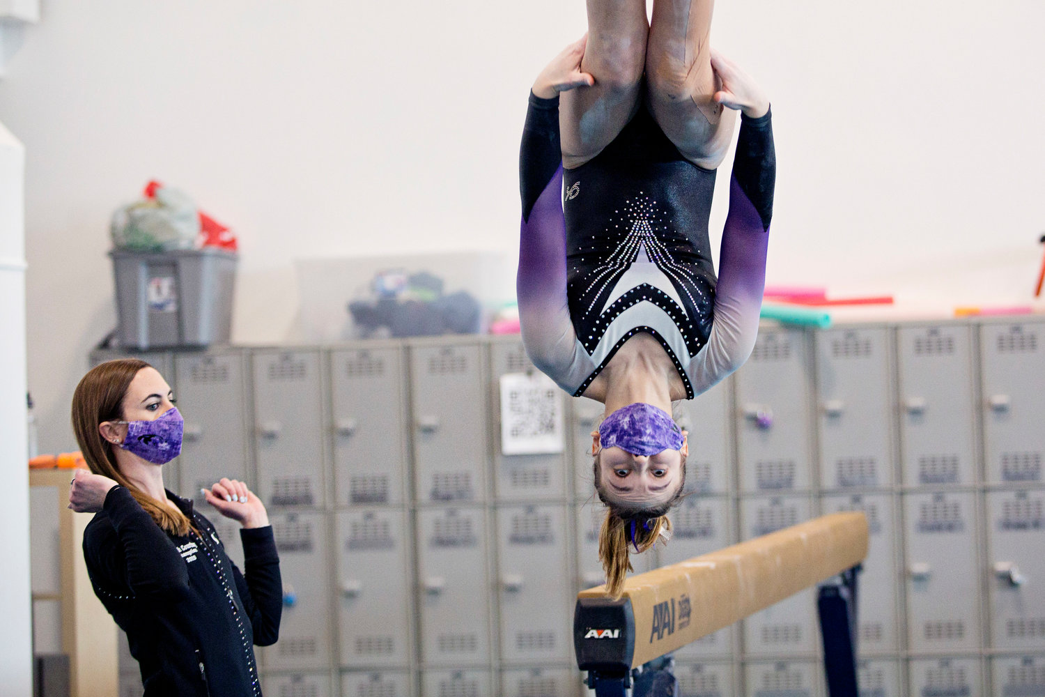 Assistant Coach Courtney L'Heureux reacts as Nora Prendergast dismounts from the beam, during the Regional State Championships.