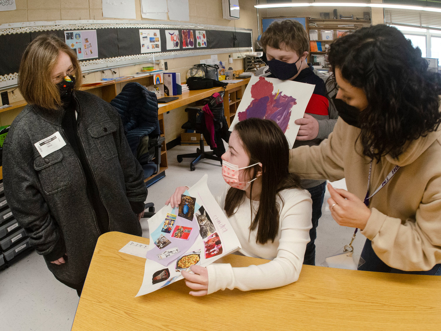 Leah Keith (left) looks on as students Claudia Rezendes and Alan Leach show their artwork with intensive classroom teacher Sabrina Sanchez at Mt. Hope High School.