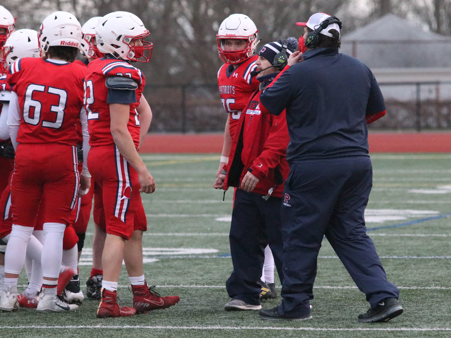 Patriots' head coach Dustin Almeida (in red) talks to his players.