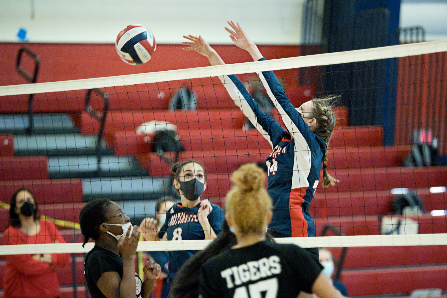 Serena Mirisola looks on as teammate Morgan Casey blocks the ball from coming over the net during Friday night's game.