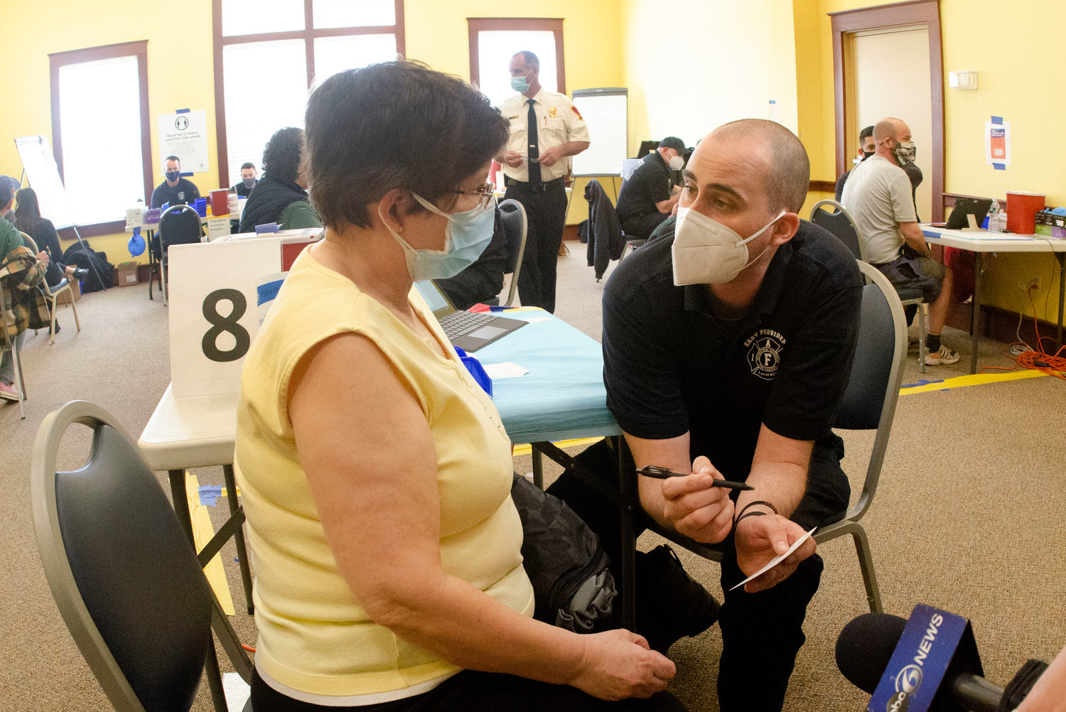East Providence firefighter Jason Andrade helps a client at the new vaccination pod.