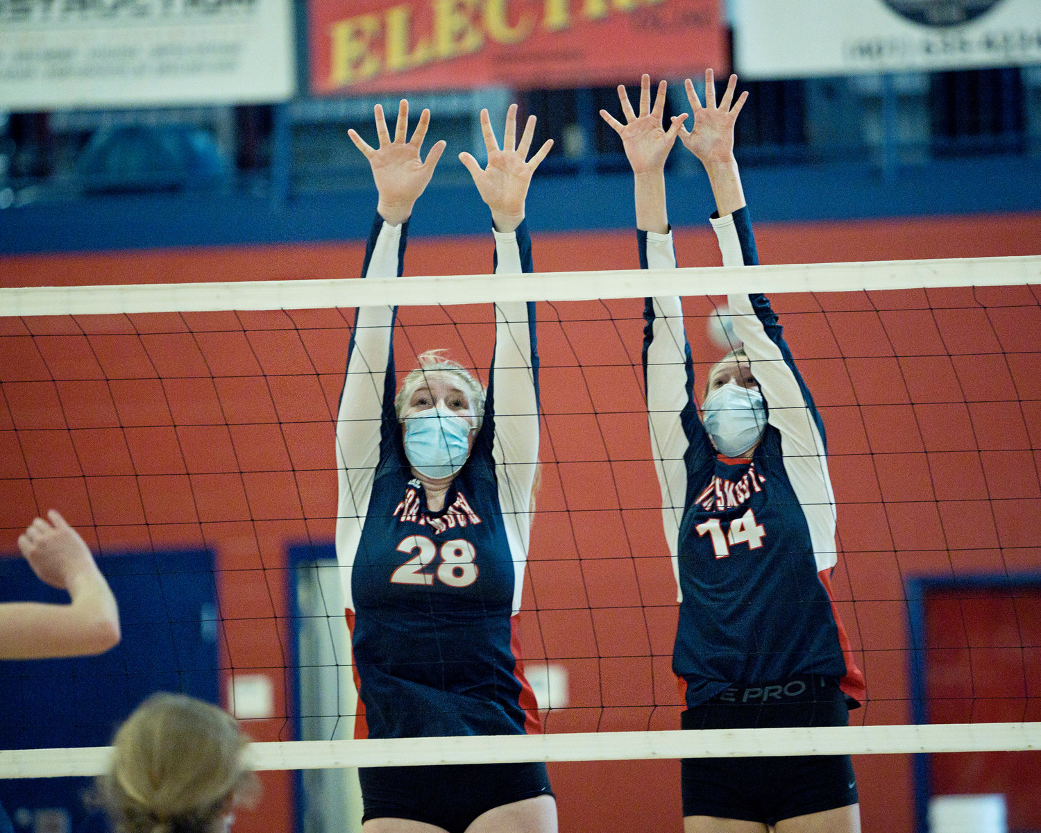 Portsmouth High's Tatum Horley (left) and Morgan Casey defend the net during Tuesday night's game against Bay View, won by the Patriots in straight sets.