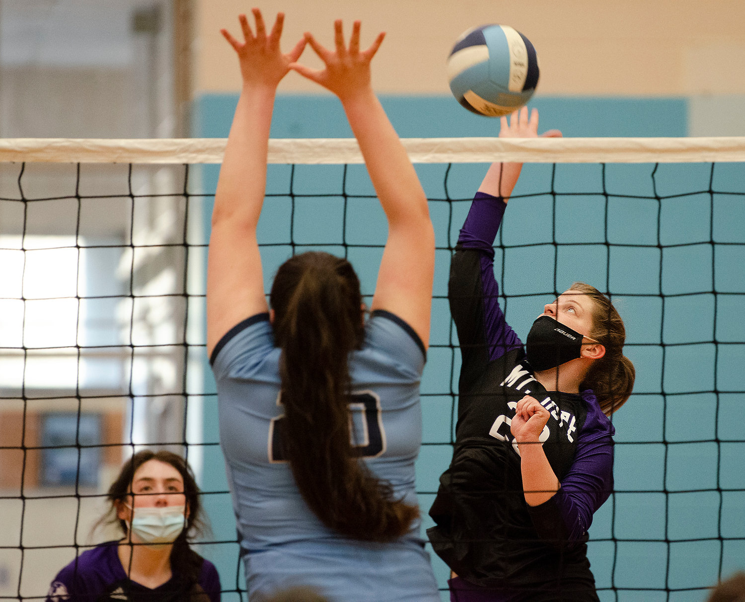 Hannah Rodriques (left) looks on as Grace Stephenson slams the ball over the net for a kill.