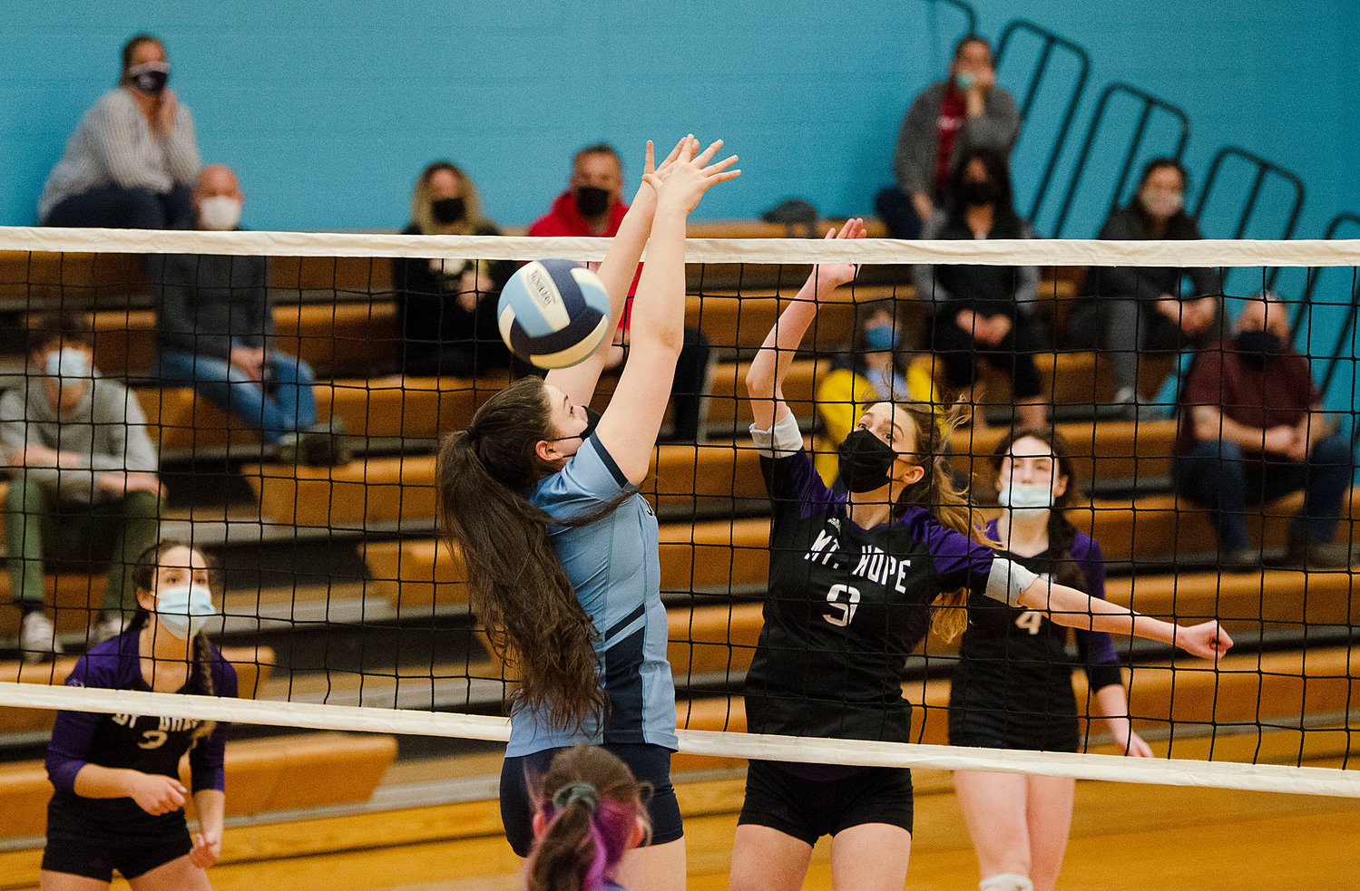 Isabel Savinon (left) and Hannah Rodriques look on as McKenna Reardon swats the ball by Johnston's Talia Laflamme.