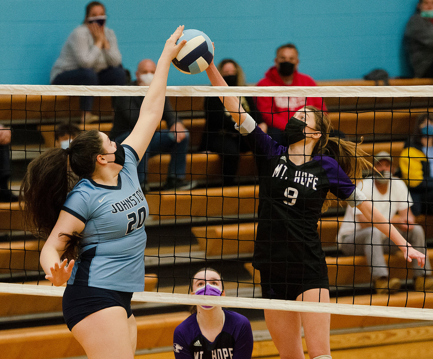 Middle hitter, McKenna Reardon (right) attempts to tip the ball by Johnston's Talia Laflamme (left) with Mia Shaw looking on.