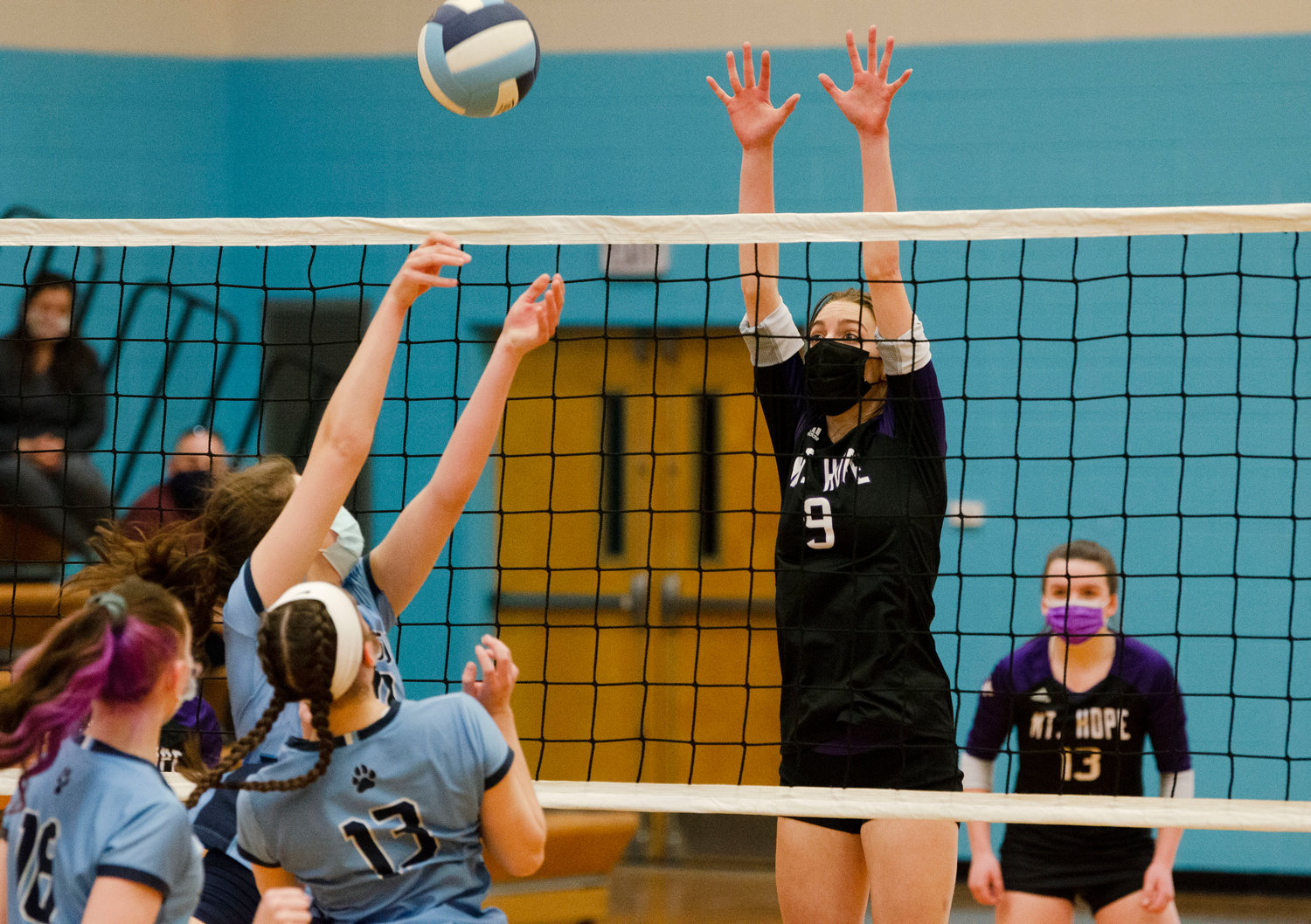 Middle hitter, McKenna Reardon (left), blocks a Panther's shot back over the net with teammate Mia Shaw looking on