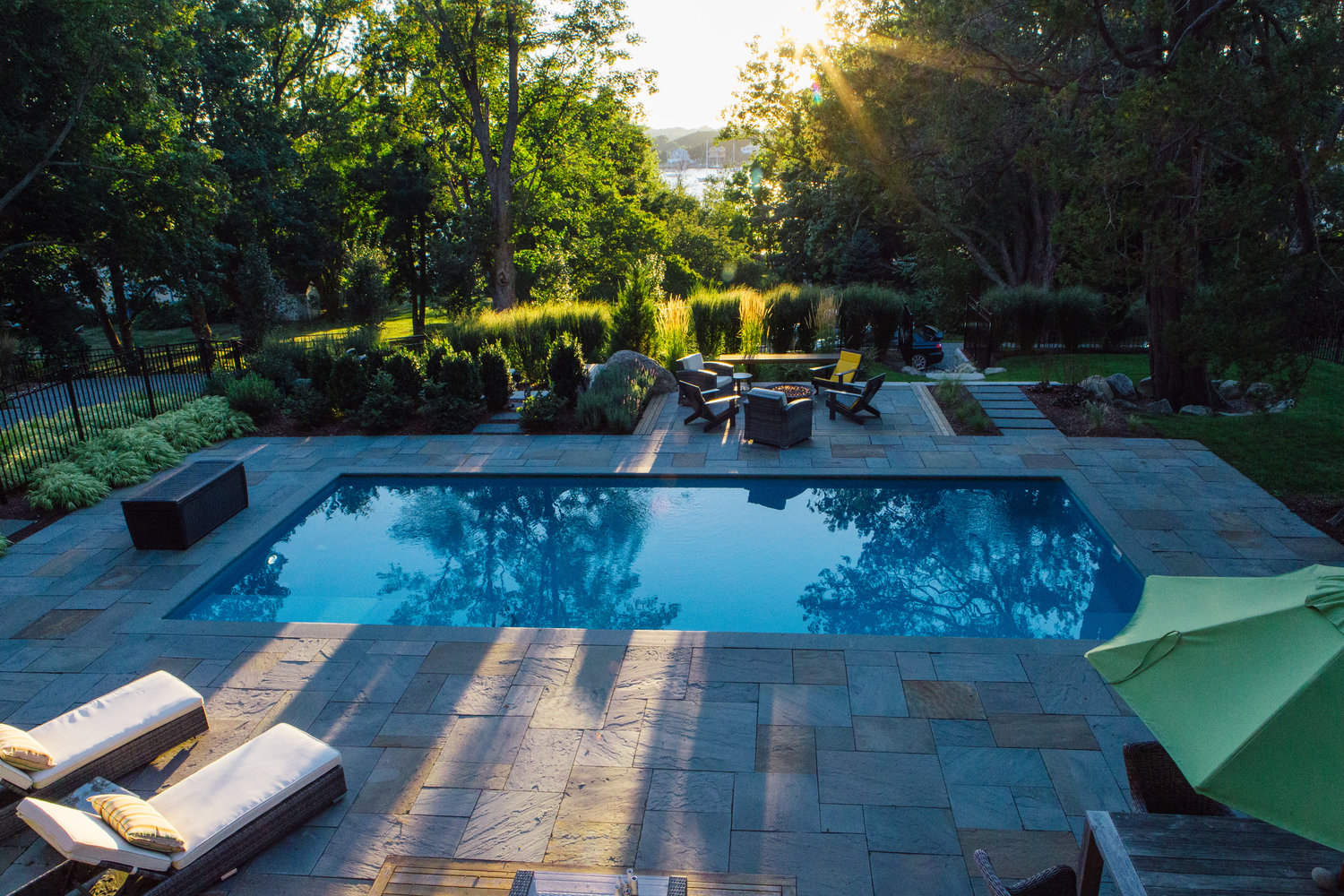 "The plantings around the pool provide both privacy and a very soft, elegant atmosphere. Brooke said: ""There were so many big trees and beautiful plantings on the site, and there was woods behind it. The whole space was surrounded by natural areas, and the homeowner really liked that look, liked the natural stone on the property, so we wanted everything with did to blend with that natural setting … In a space like this you want to clean it up, but make it feel like it's always been there."""