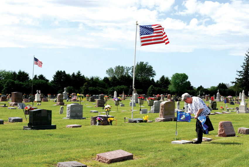MEMORIAL DAY -- An American flag is placed at the graves of military personnel and a blue VFW Auxiliary flag is placed at the graves of members to the organization. VFW Auxiliary president Lou Ann Huberty is pictured placing a flag at a grave site Tuesday afternoon. Memorial Day services will be held Monday, May 31, along the shores of Five Island Lake and at the cemetery. In case of inclement weather, Memorial Day services will be held at the VFWPost Home.                                                                                    --Jane Whitmore photo